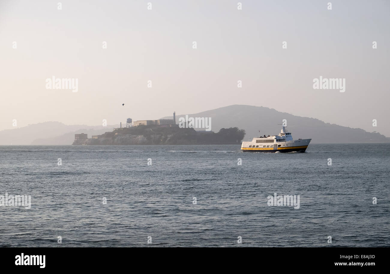 Alcatraz island prison in the mist with a tour boat in the foreground - Stock Image