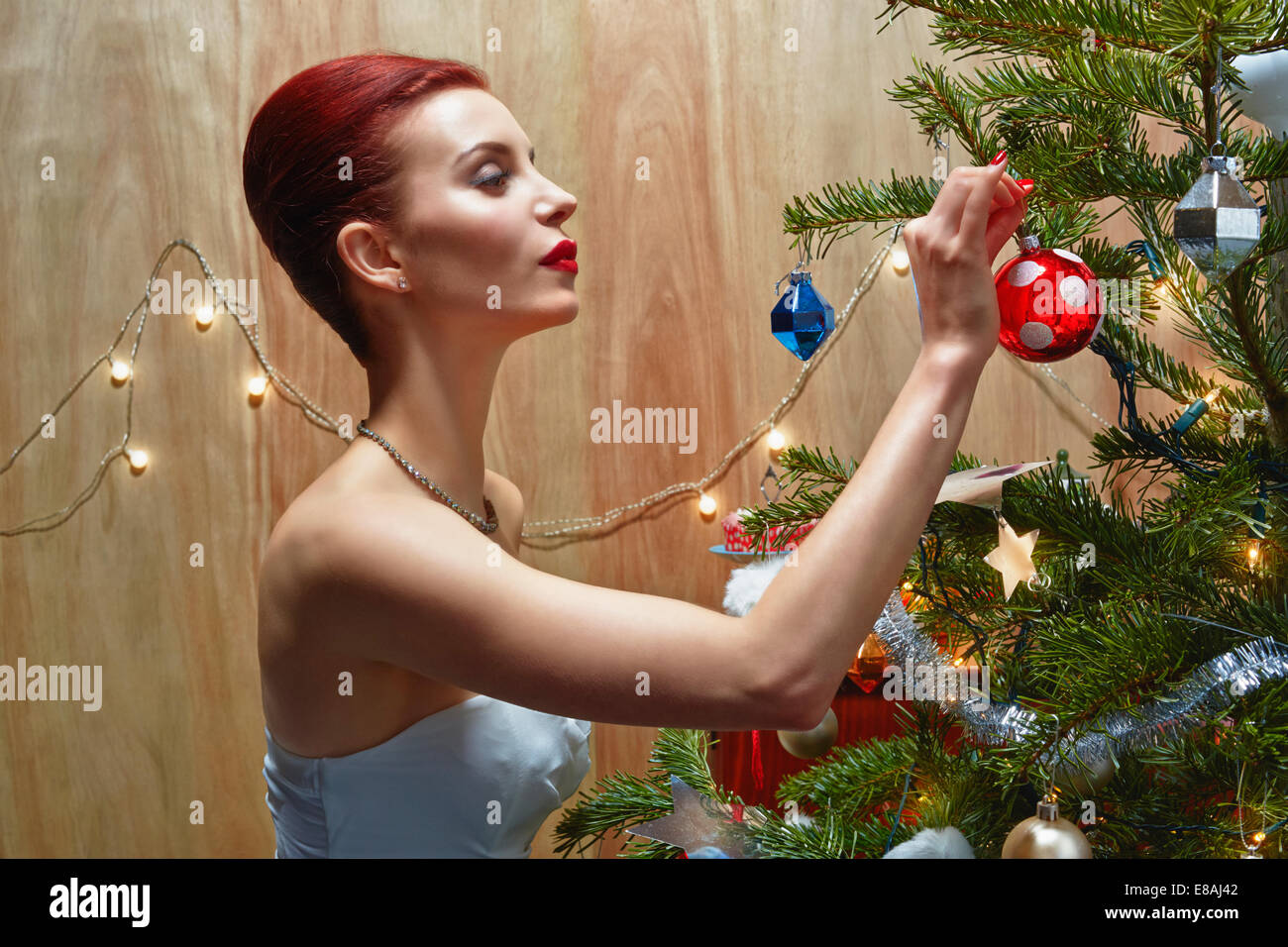 Woman decorating Christmas tree - Stock Image