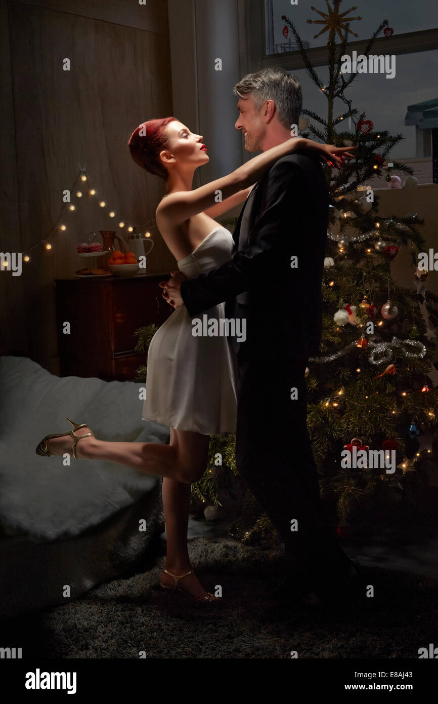 Husband and wife dancing by Christmas tree - Stock Image