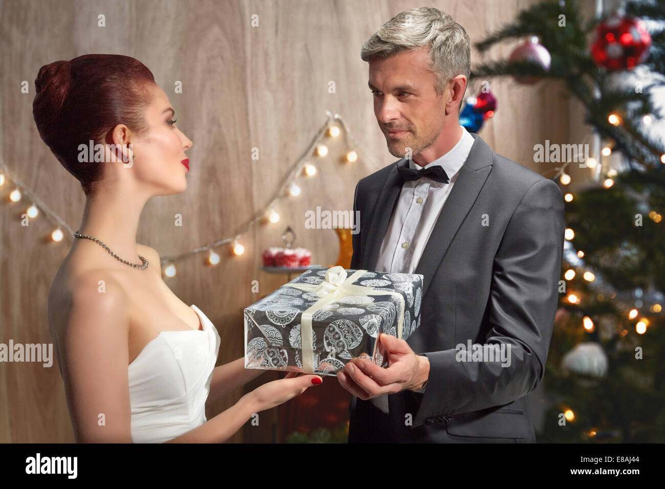Husband and wife with Christmas gift - Stock Image
