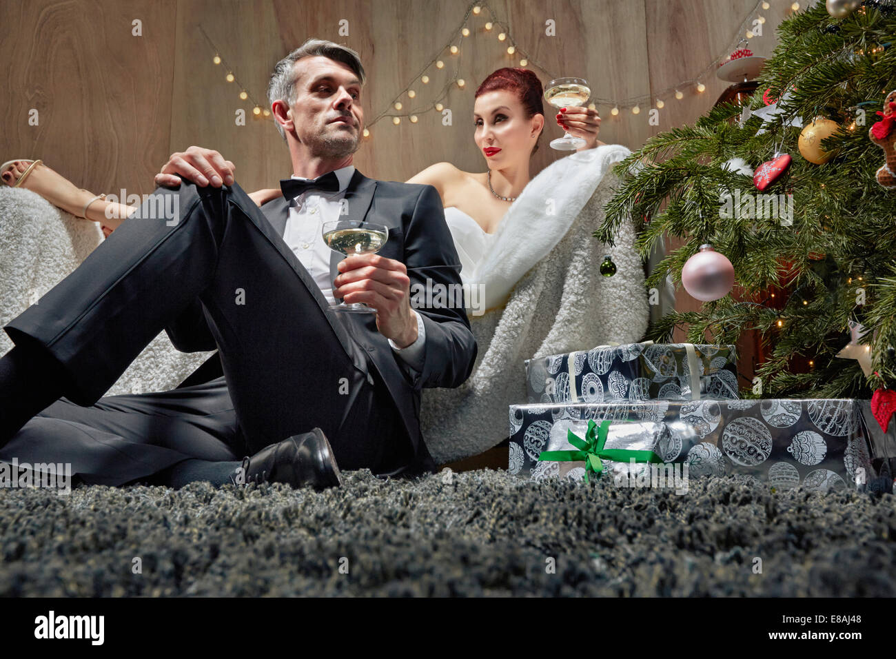 Husband and wife lounging by Christmas tree - Stock Image