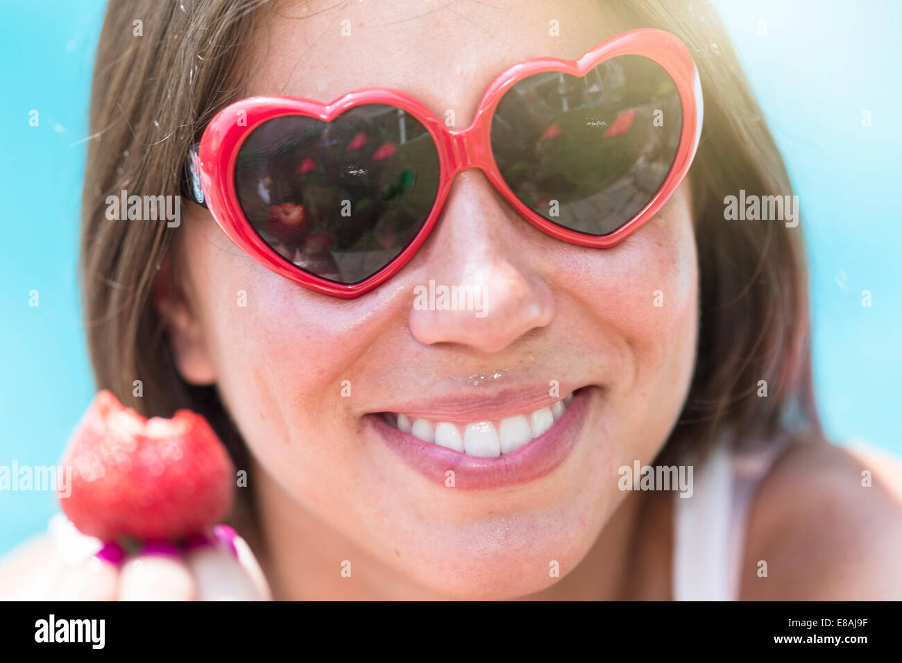 Close up portrait of young woman eating strawberry - Stock Image