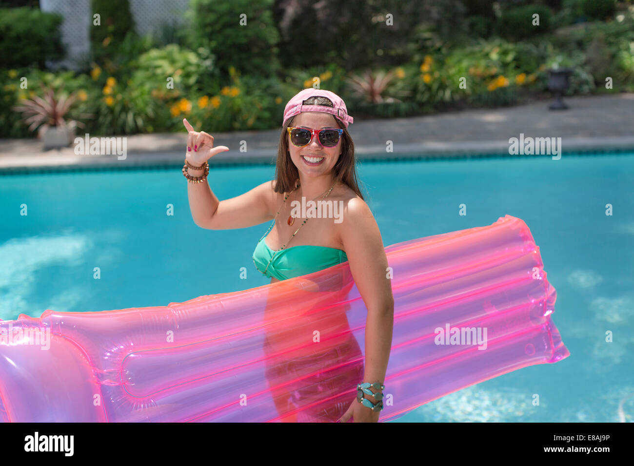 Portrait of young woman making hang loose sign at poolside - Stock Image
