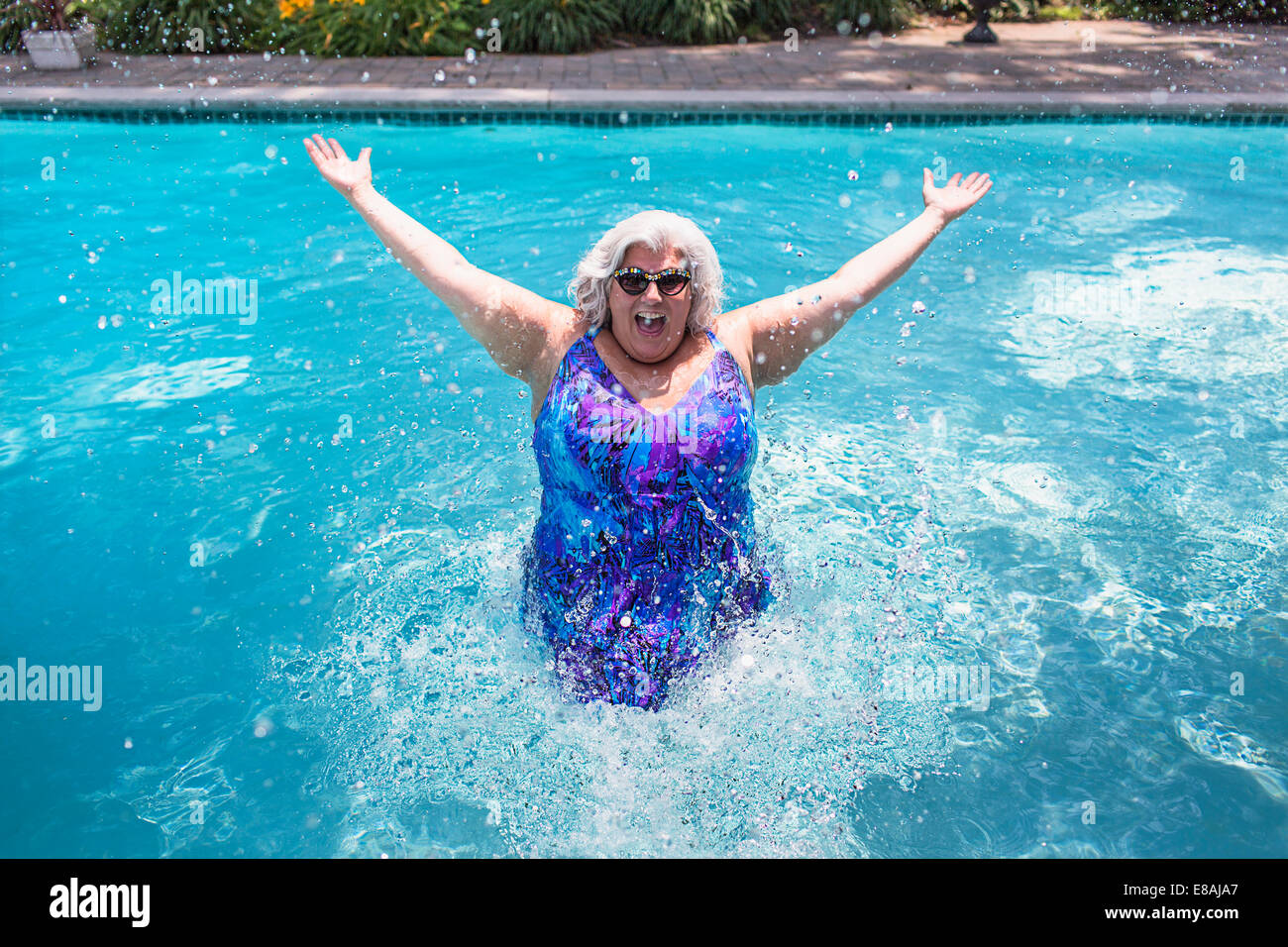Portrait of mature woman splashing about in swimming pool - Stock Image