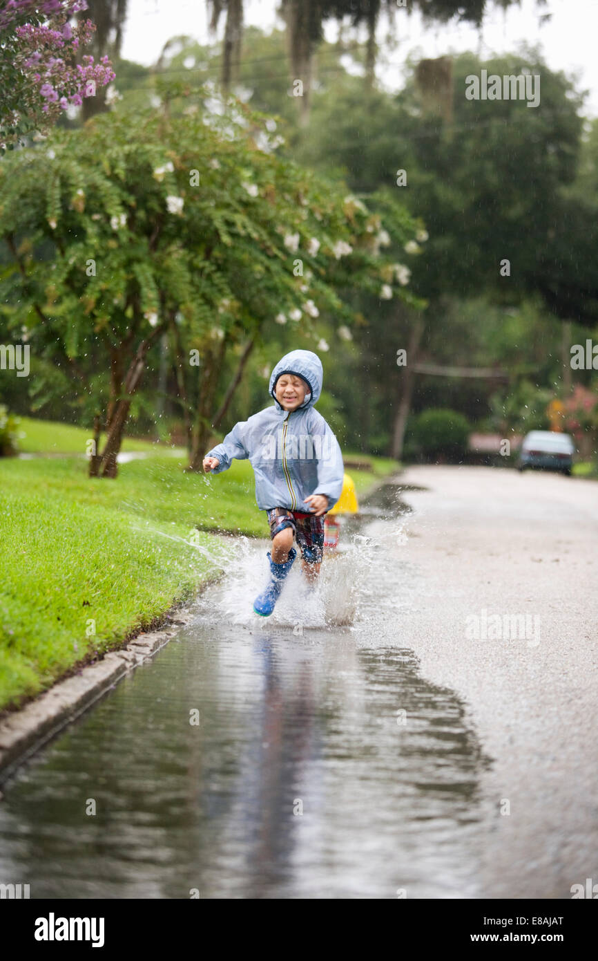 Boy in rubber boots running and splashing in rain puddle - Stock Image