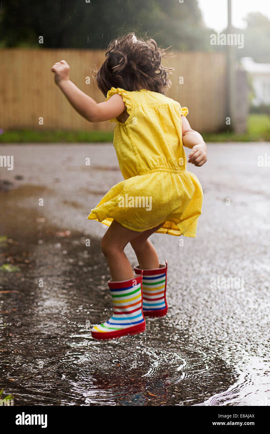 Girl wearing rubber boots jumping in rain puddle - Stock Image