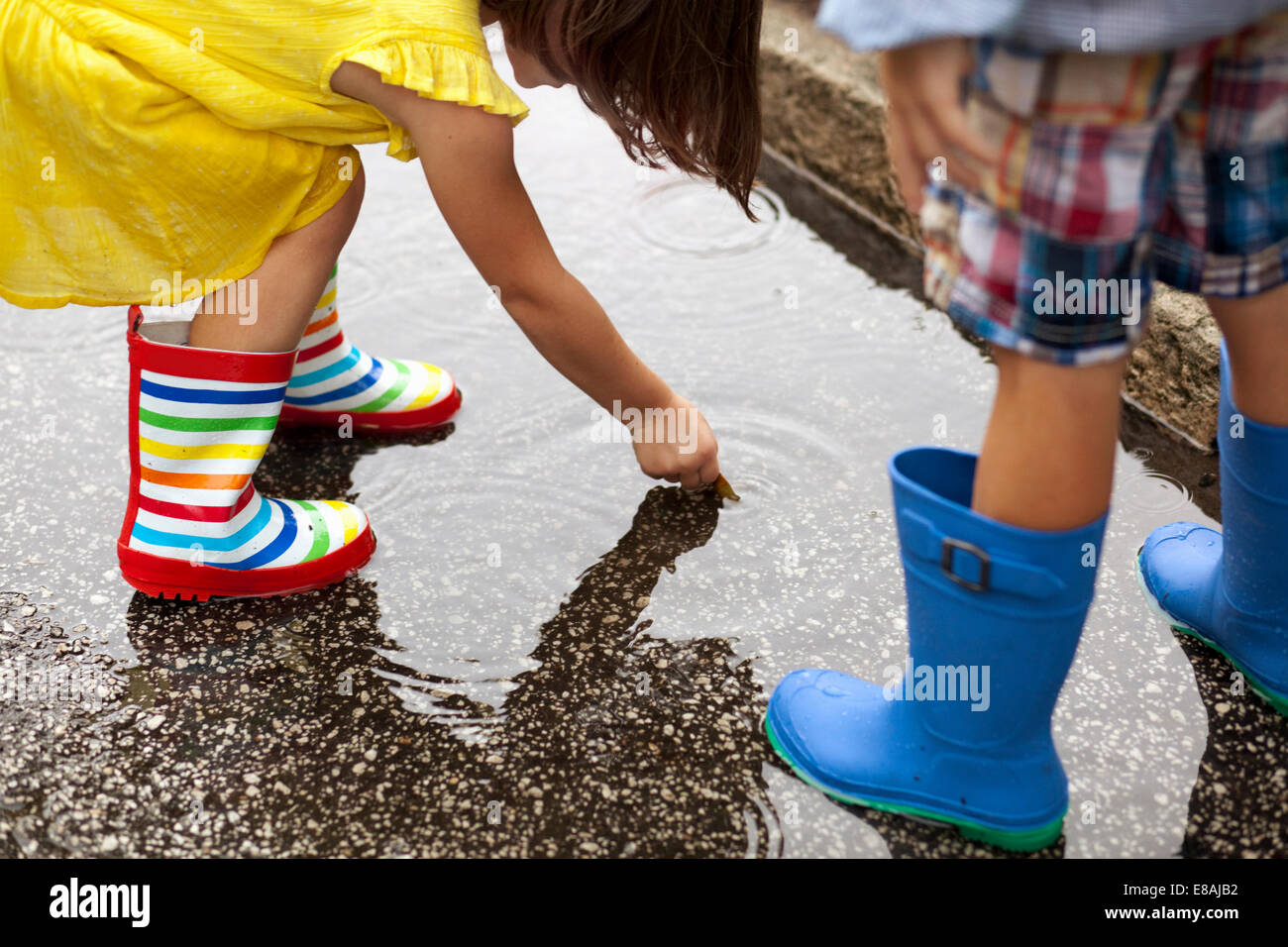 Boy and sister wearing rubber boots looking down at in rain puddle - Stock Image