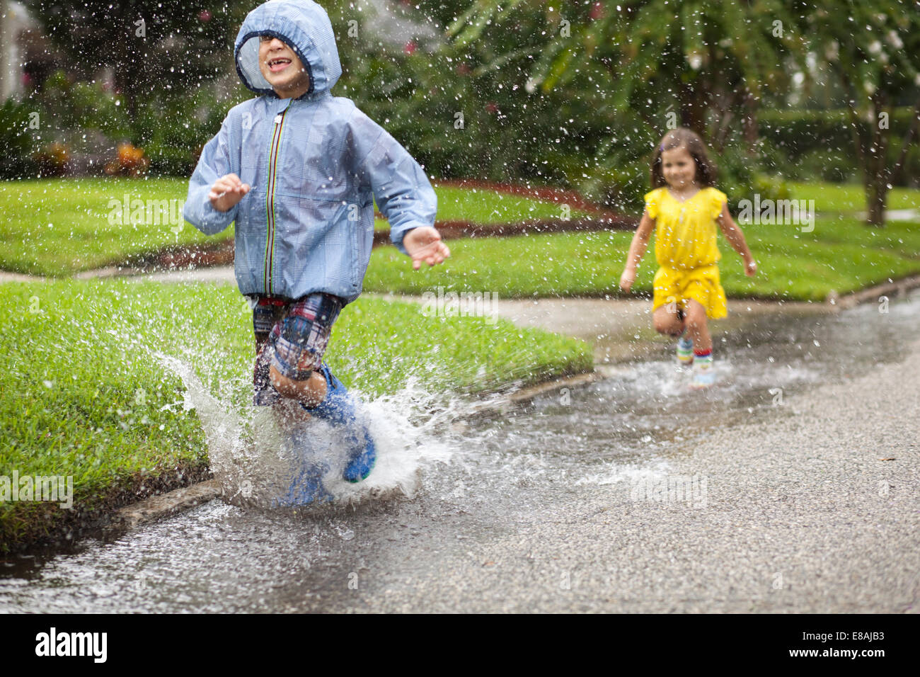 Boy and sister wearing rubber boots running and splashing in rain puddle - Stock Image