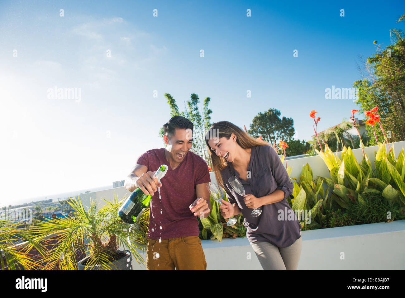 Couple opening champagne in penthouse rooftop garden, La Jolla, California, USA - Stock Image