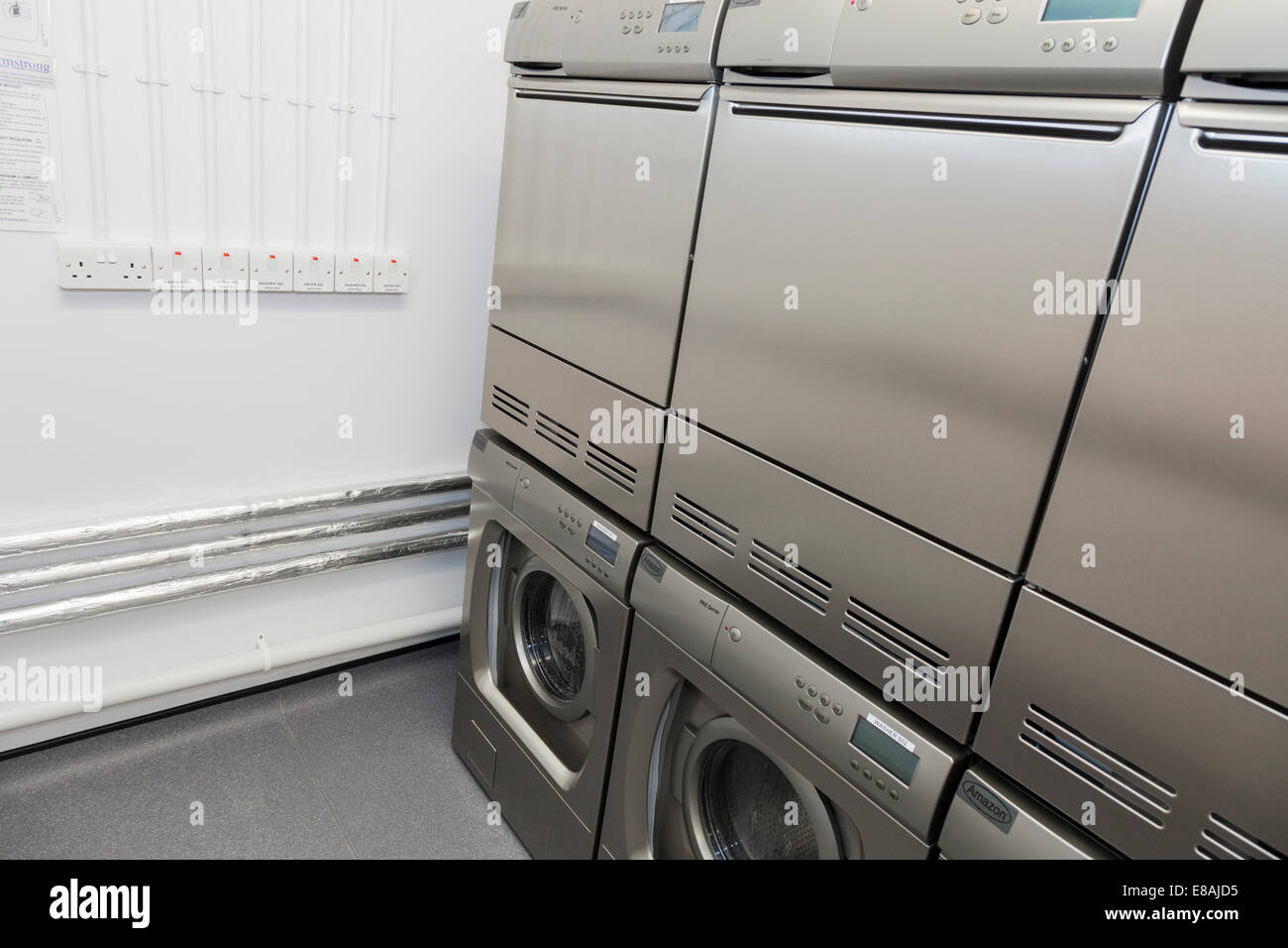 Washing machines and tumble dryers in Communal Laundry room. - Stock Image
