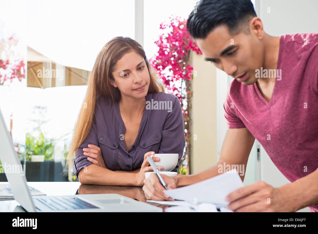 Worried couple checking bills and paperwork in dining room - Stock Image