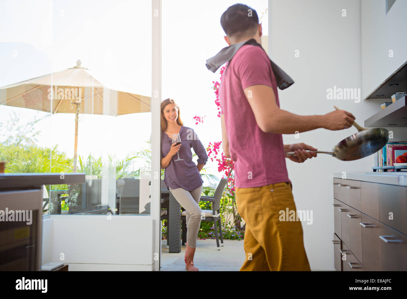 Couple cooking and drinking wine in kitchen - Stock Image