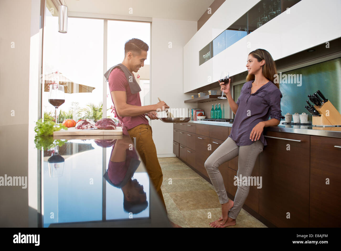 Couple chatting and drinking wine whilst cooking in kitchen - Stock Image