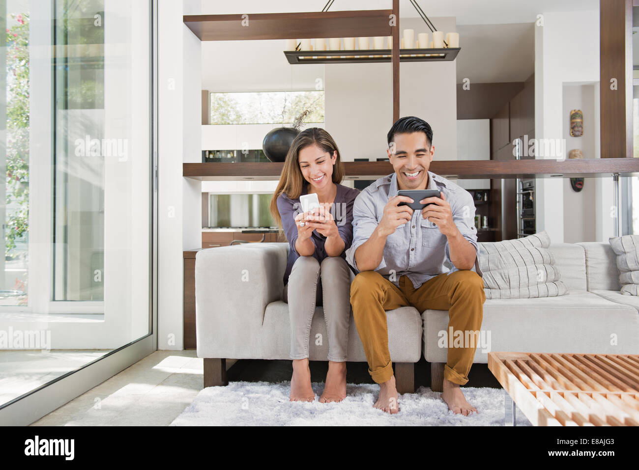 Couple playing games on smartphones on sitting room sofa - Stock Image