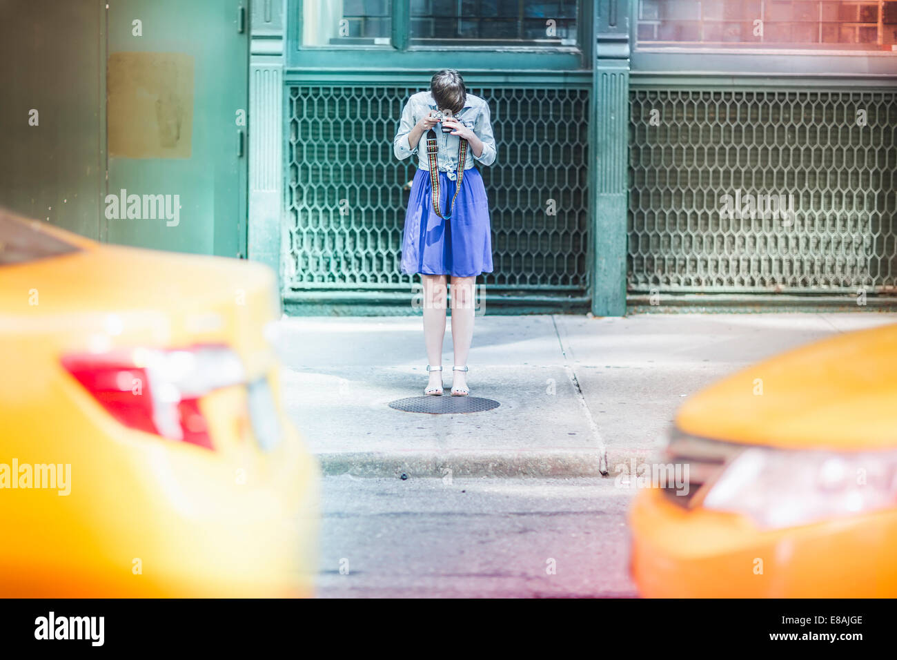 Woman photographing on street, New York, US - Stock Image