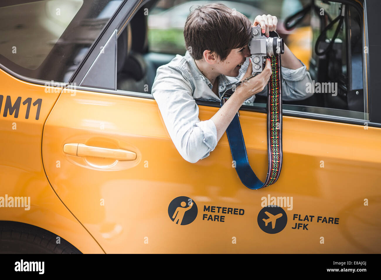 Woman photographing from yellow taxi, New York, US - Stock Image