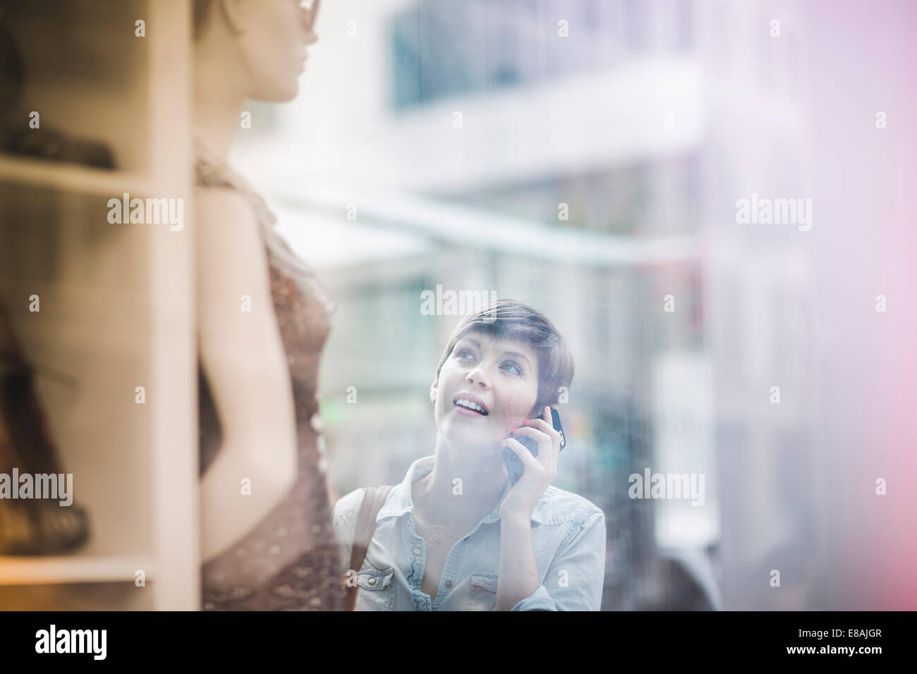Shopper looking at shop window, New York, US - Stock Image