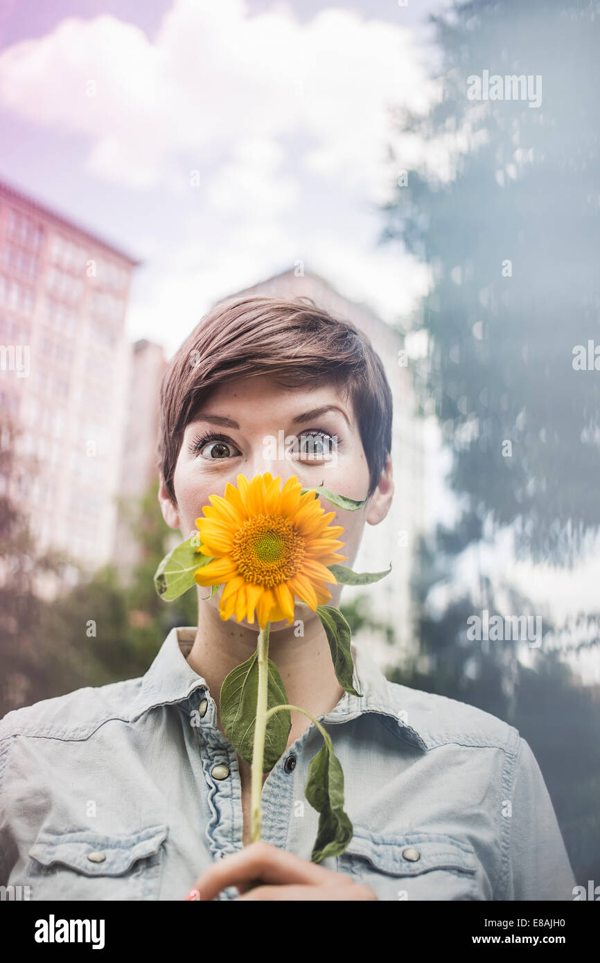 Woman covering mouth with flower - Stock Image