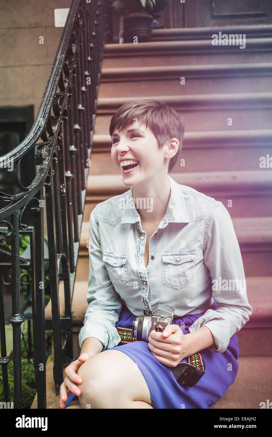Young woman sitting on steps with camera, New York, US - Stock Image