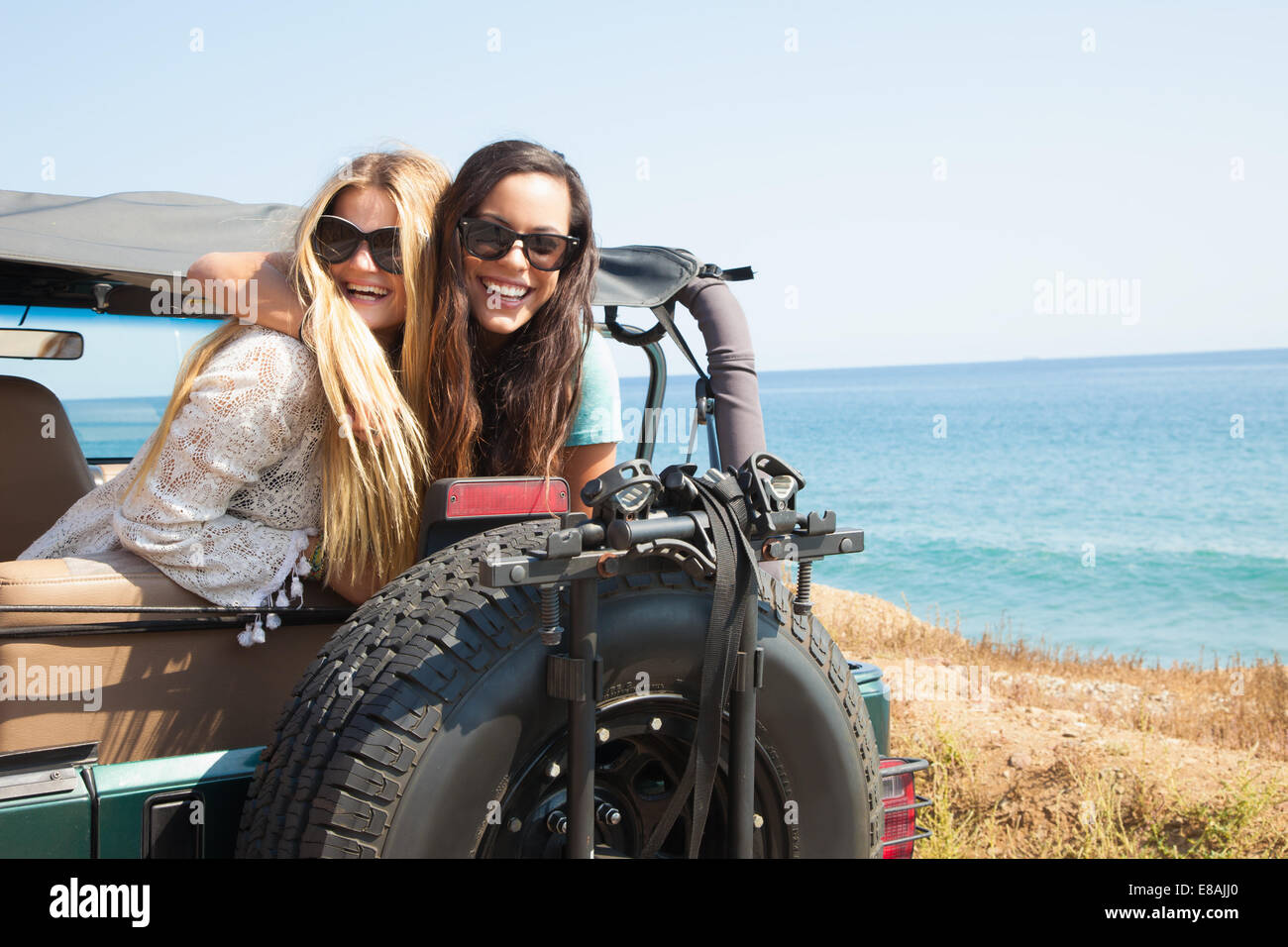 Portrait of two young women leaning out of jeep at coast, Malibu, California, USA - Stock Image