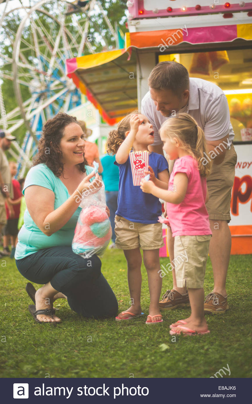 Mid adult couple and two young daughters eating popcorn and candyfloss at funfair - Stock Image