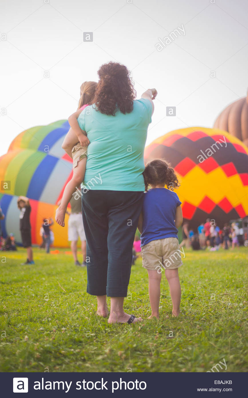 Rear view of mid adult woman and two daughters watching hot air balloons inflating at festival - Stock Image