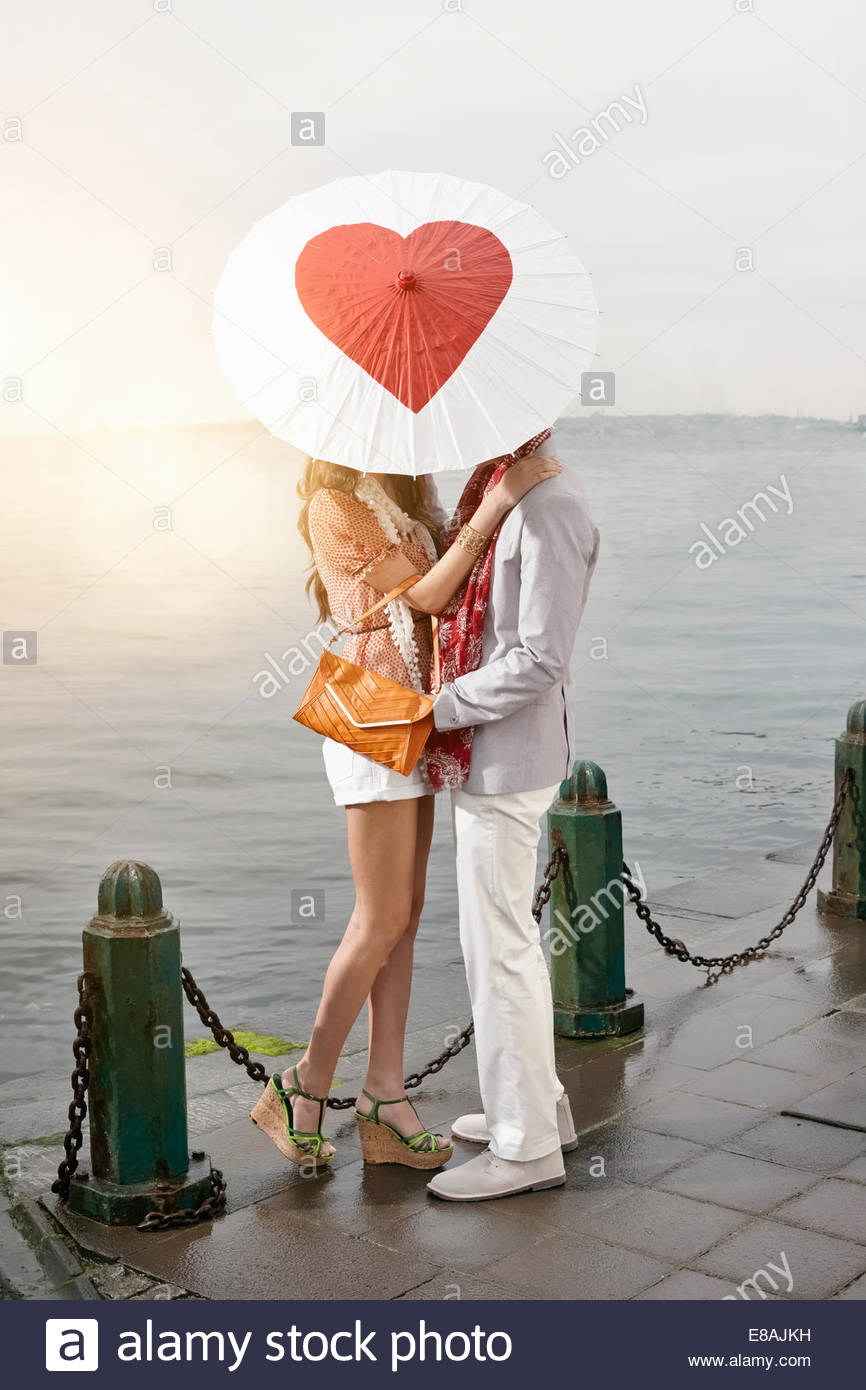 Romantic young couple behind heart umbrella with arms around each other on lakeside - Stock Image