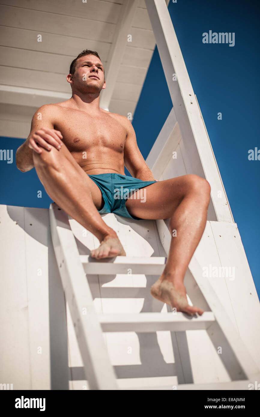 Young male lifeguard watching from lifeguard tower, Castiadas, Sardinia, Italy Stock Photo