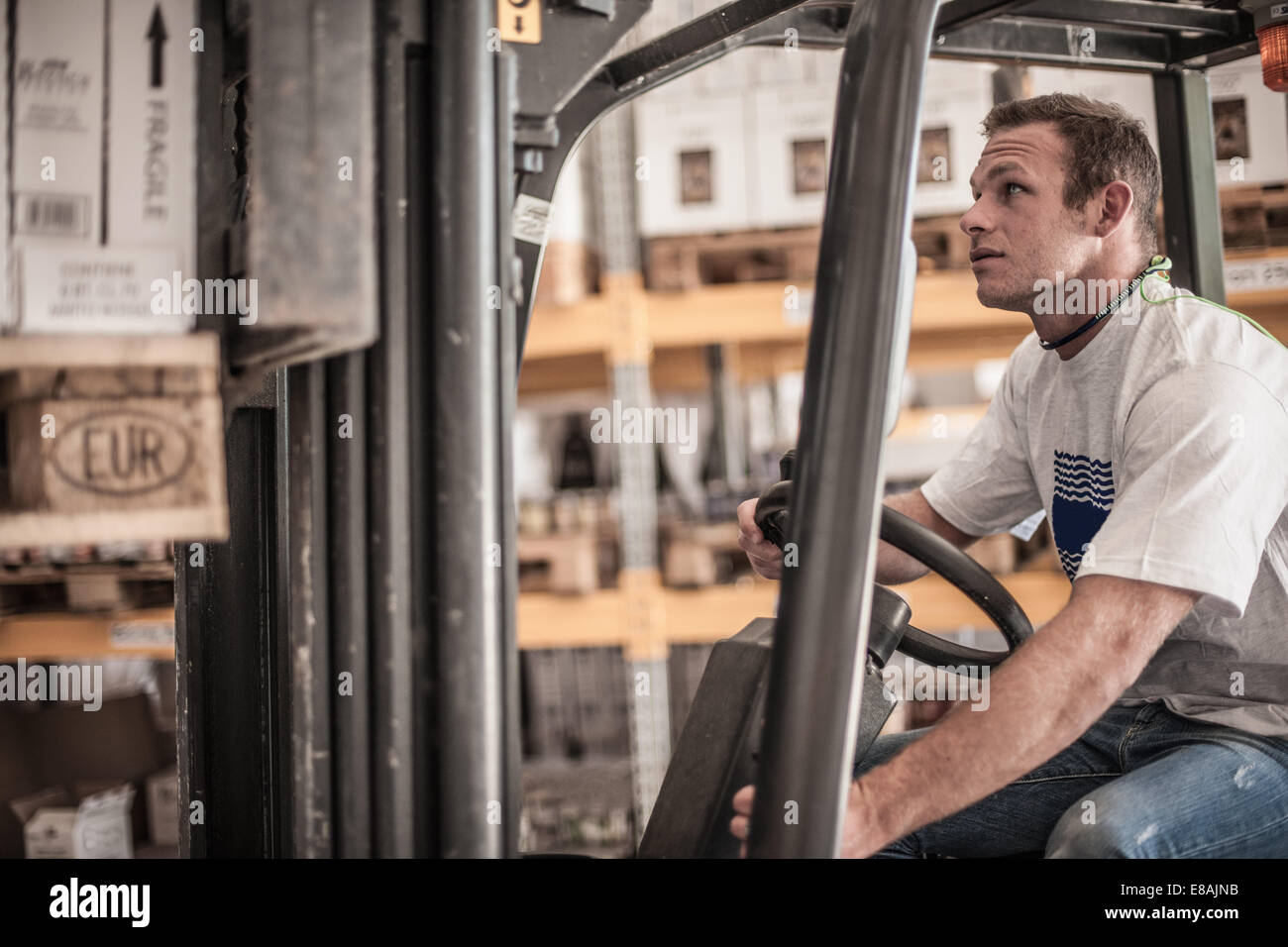 Young man driving forklift truck in factory warehouse - Stock Image