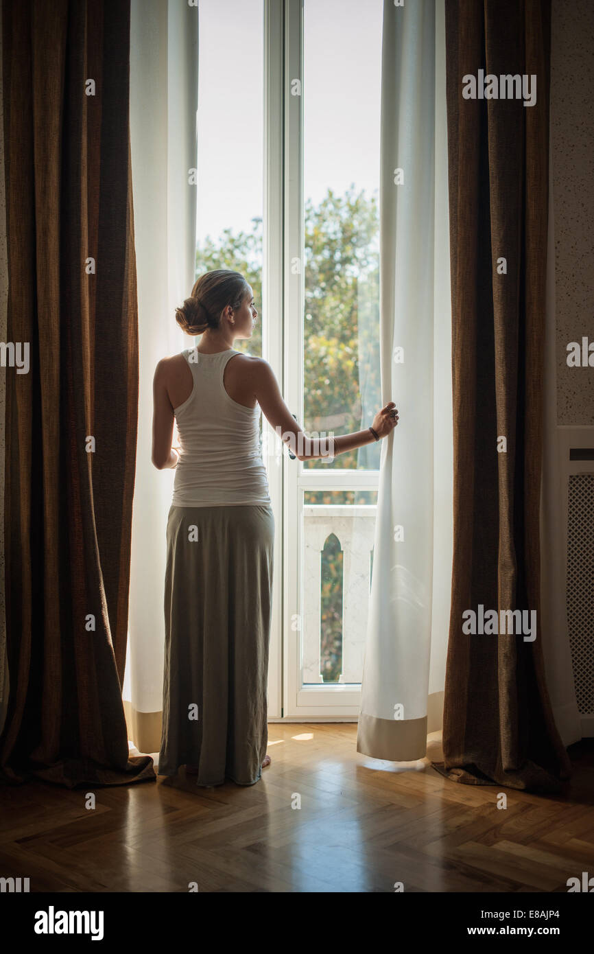 Elegant young woman looking out of sitting room windows - Stock Image