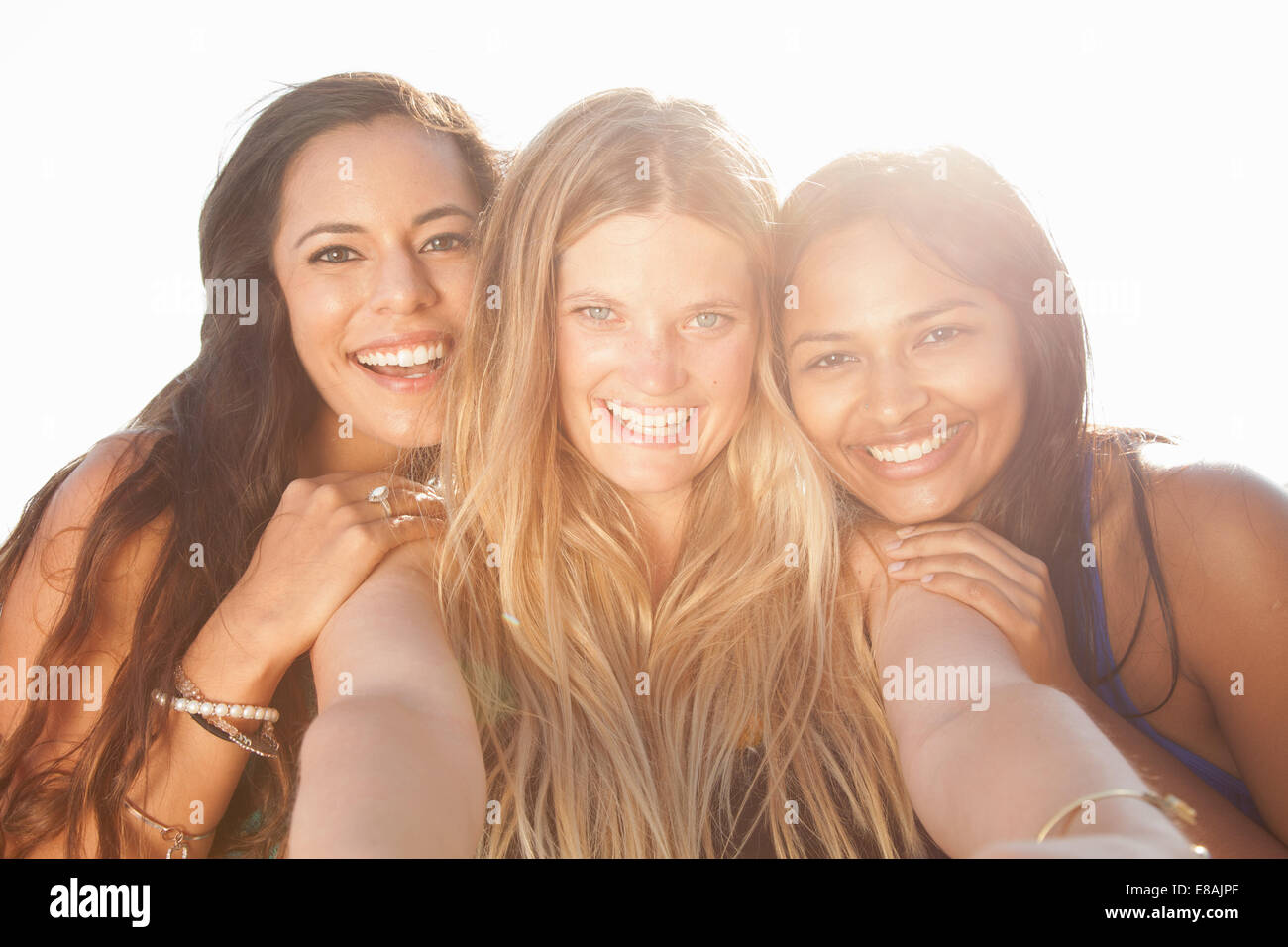 Three smiling young women taking a self portrait - Stock Image