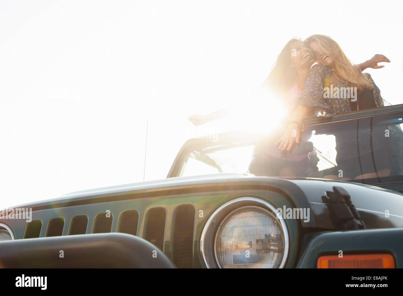 Two young women standing up in back of jeep - Stock Image