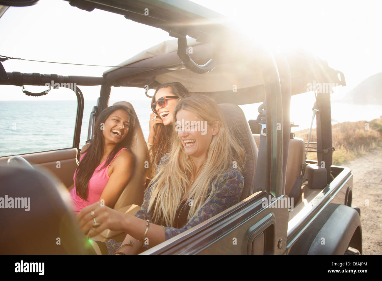 Three young women driving in jeep at coast, Malibu, California, USA - Stock Image