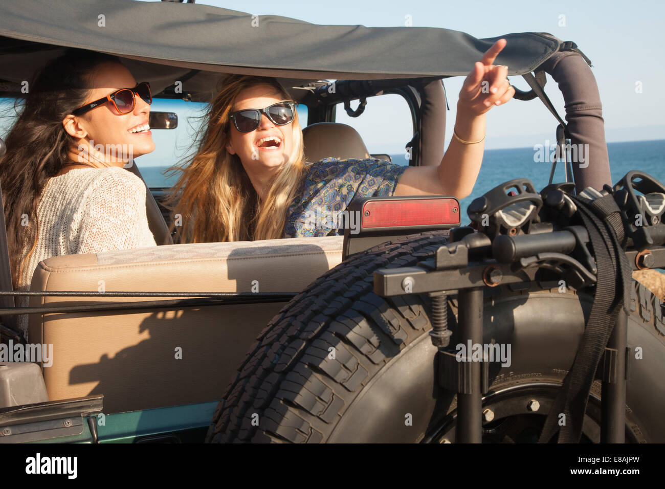 Two young women looking up from jeep at coast, Malibu, California, USA - Stock Image