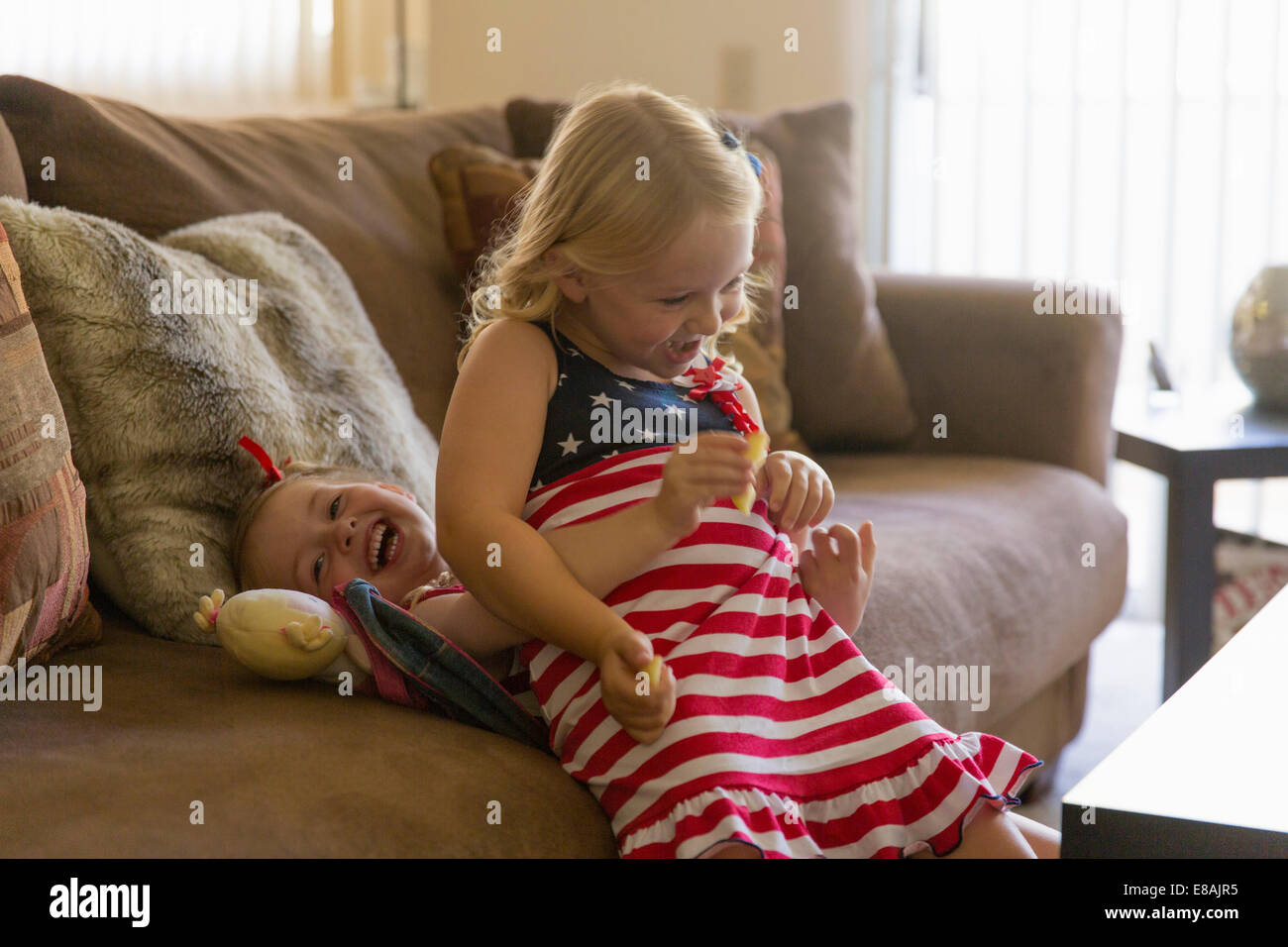 Girl sitting on top of older sister on sofa - Stock Image