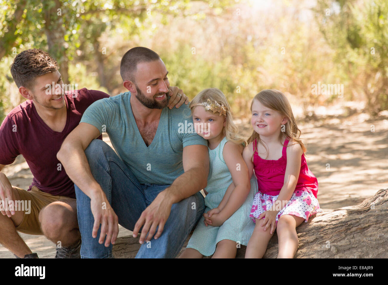 Male couple sitting on riverbank with two daughters - Stock Image