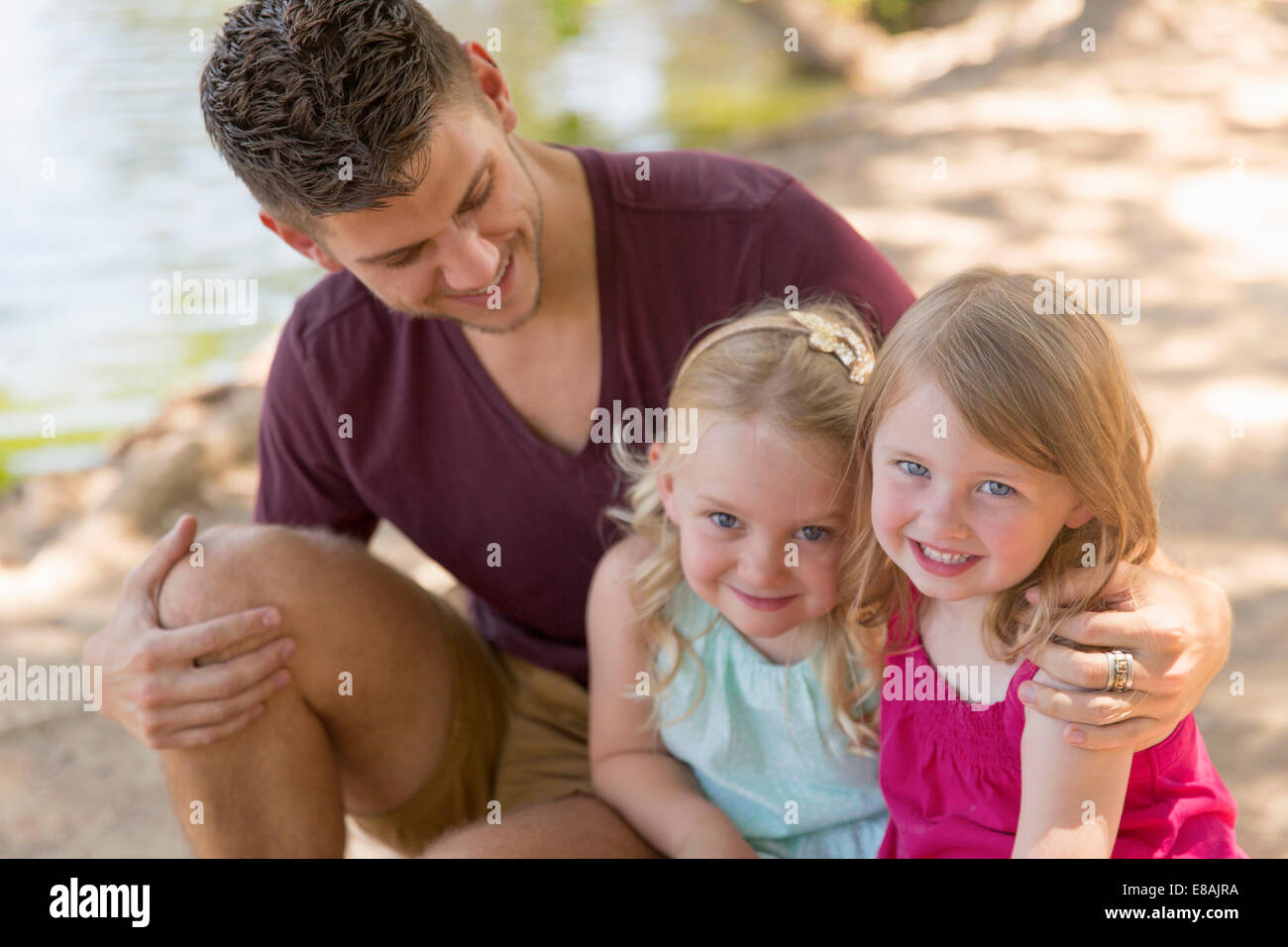 Portrait of father and two daughters on riverbank - Stock Image