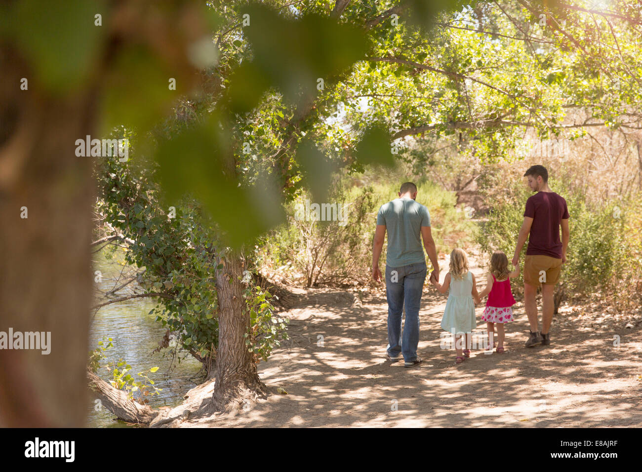 Rear view of male couple strolling with two daughters in park - Stock Image