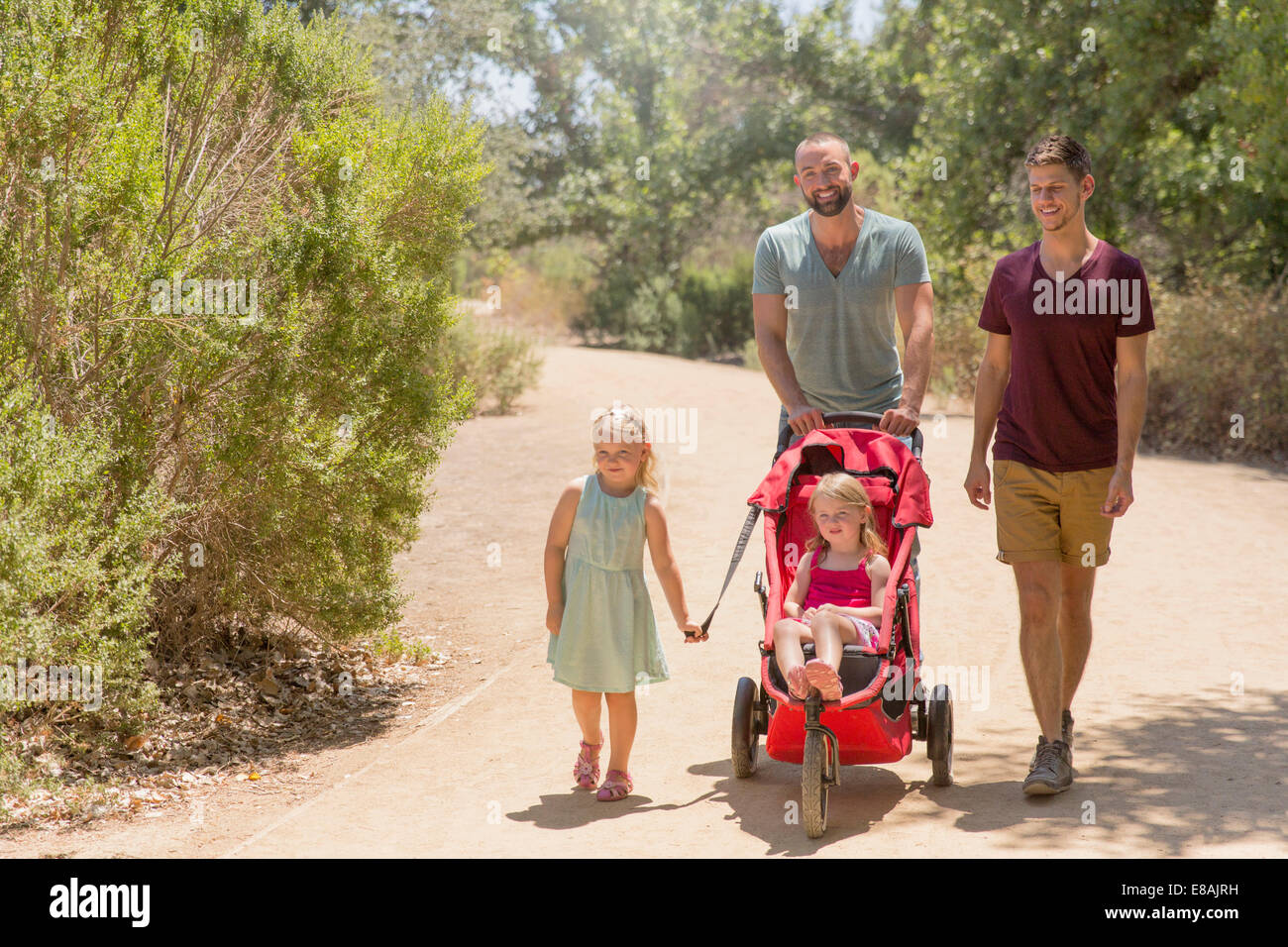 Male couple strolling with two daughters in park Stock Photo