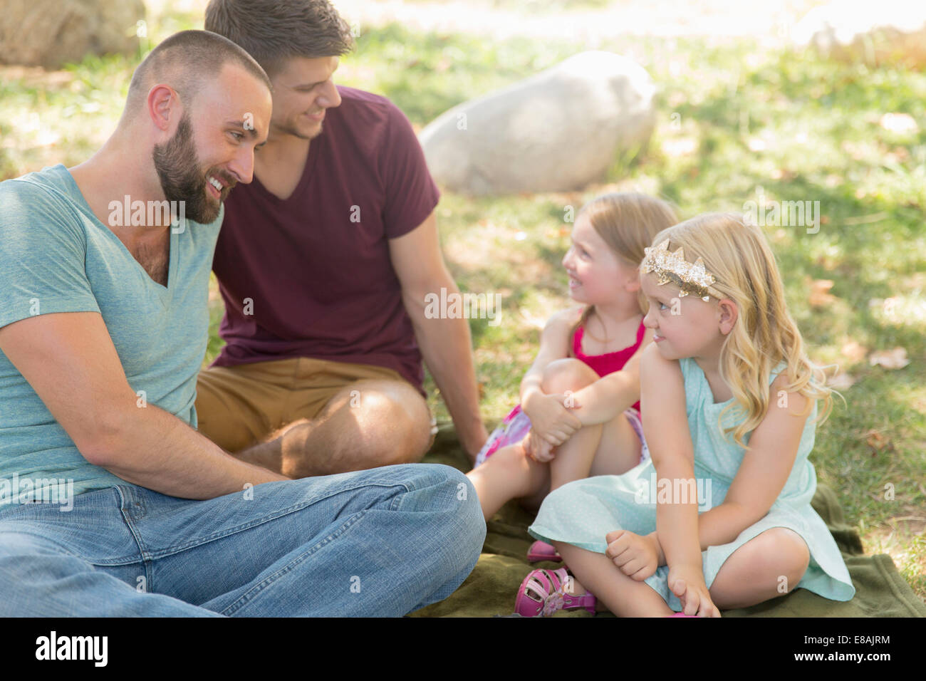 Two sisters and fathers sitting chatting in park - Stock Image
