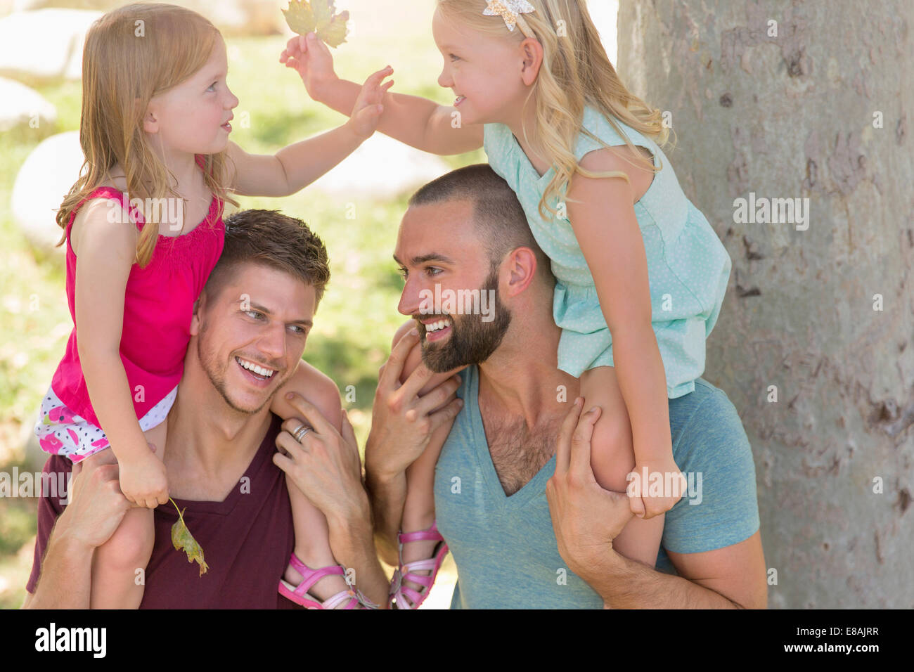 Two sisters sitting on fathers shoulders in park - Stock Image
