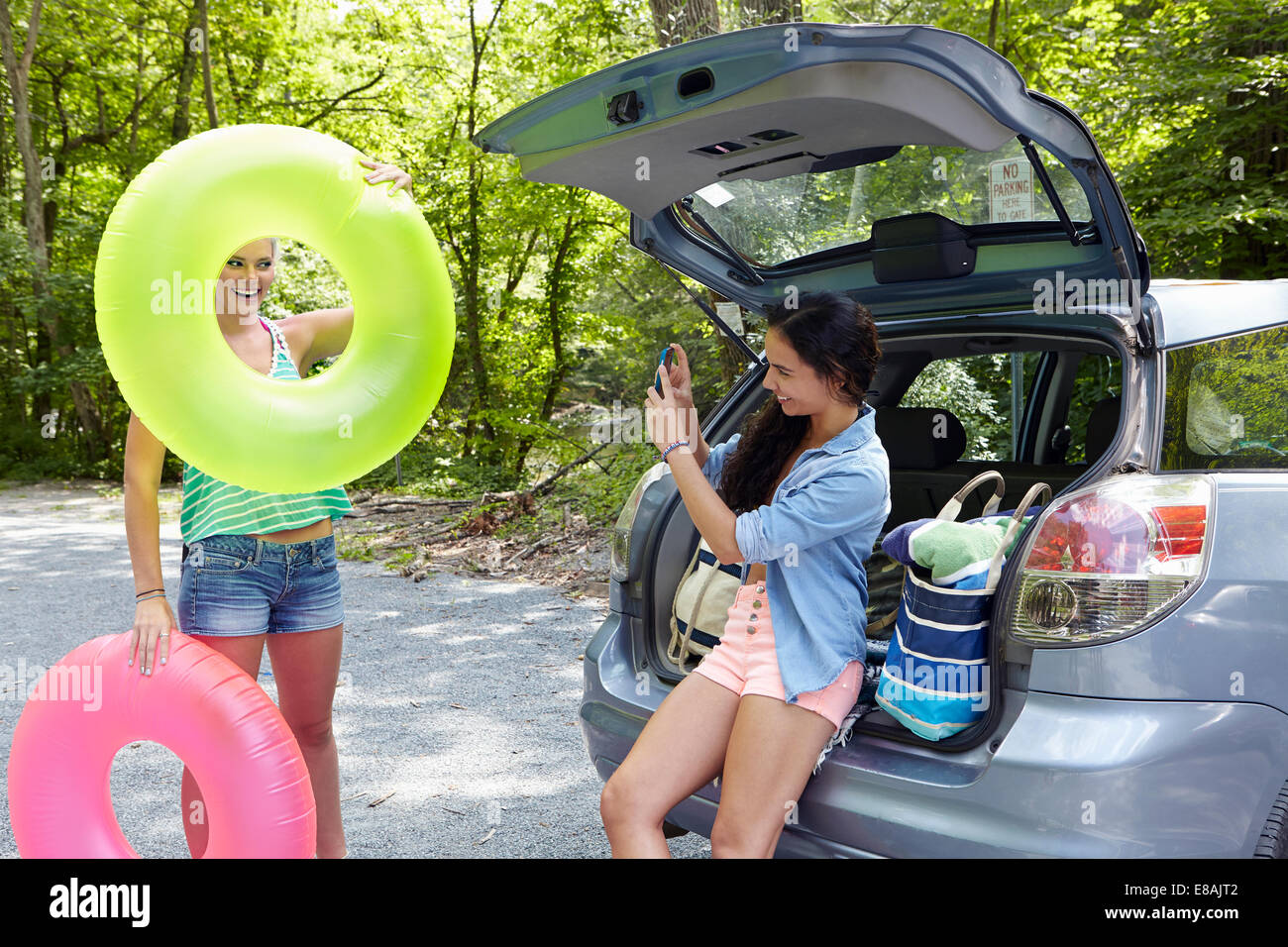 Hikers sitting at rear of car photographing - Stock Image