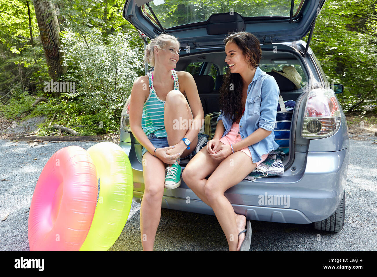 Hikers sitting at rear of car with inflatable rings - Stock Image