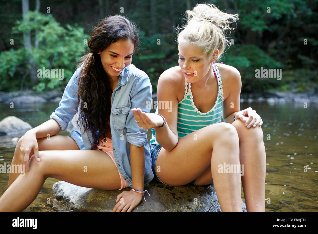 Women sitting by river in forest - Stock Image