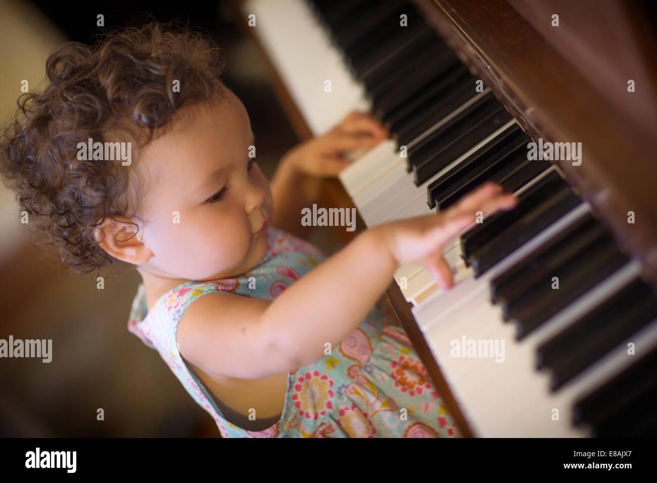 Cute baby girl playing piano Stock Photo