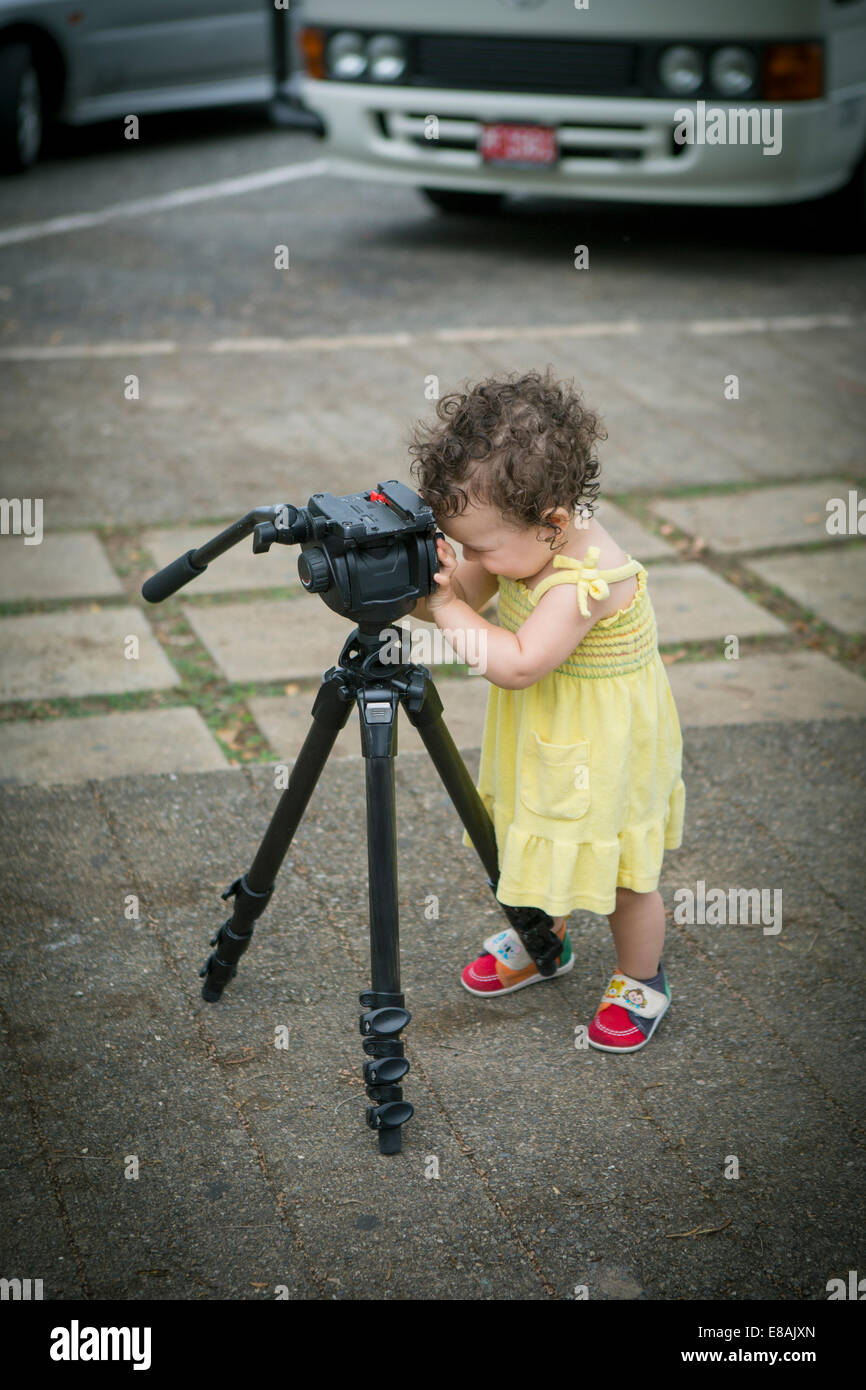 Cute baby girl playing with a tripod - Stock Image
