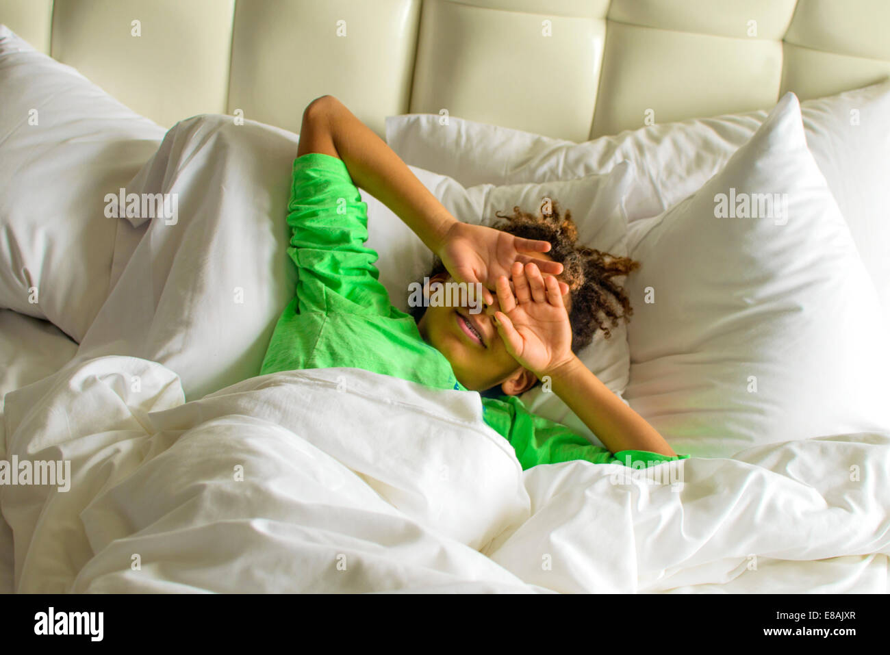 Sleepy boy lying in bed shielding face with hands - Stock Image
