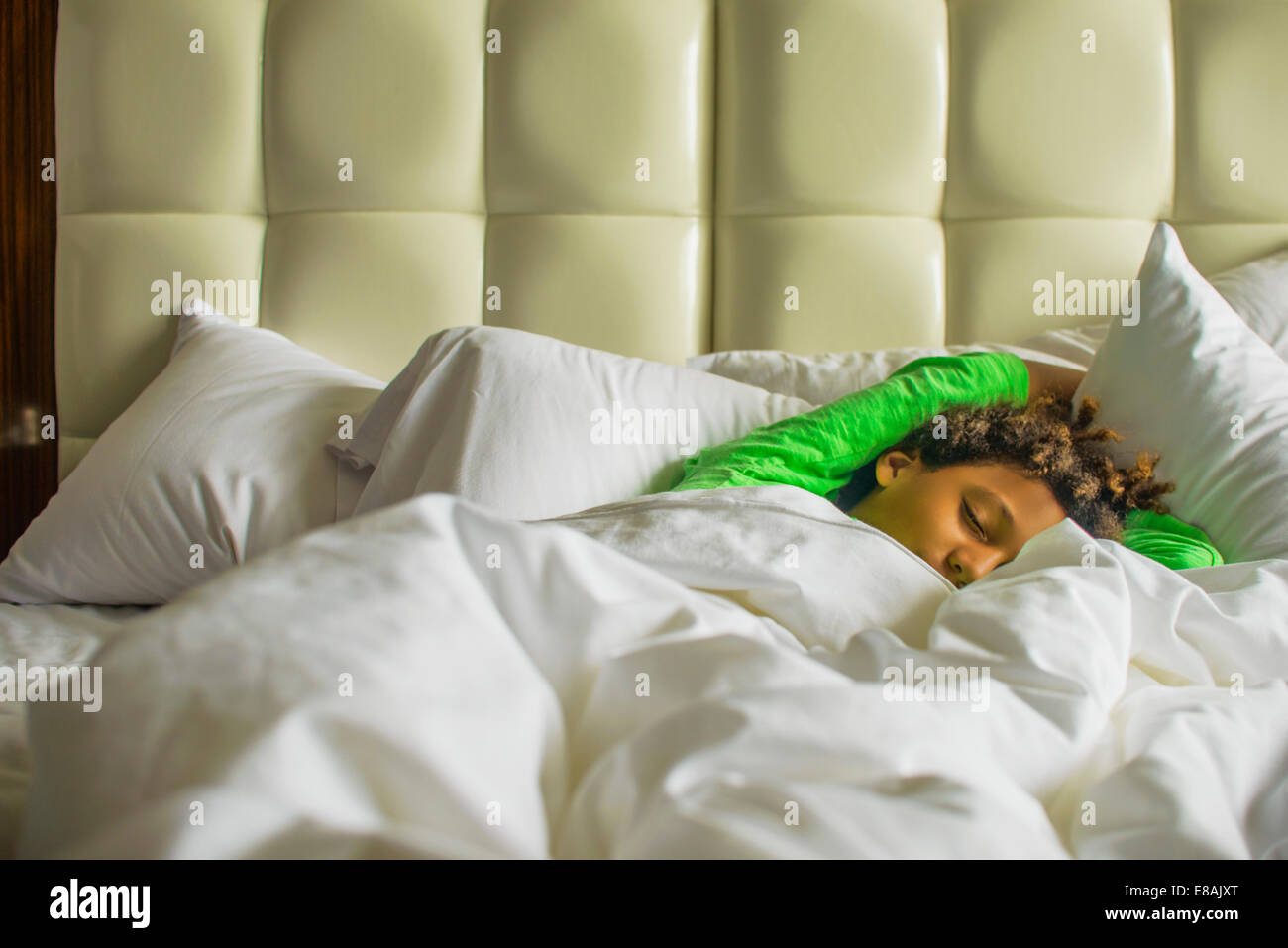 Boy lying asleep in bed - Stock Image