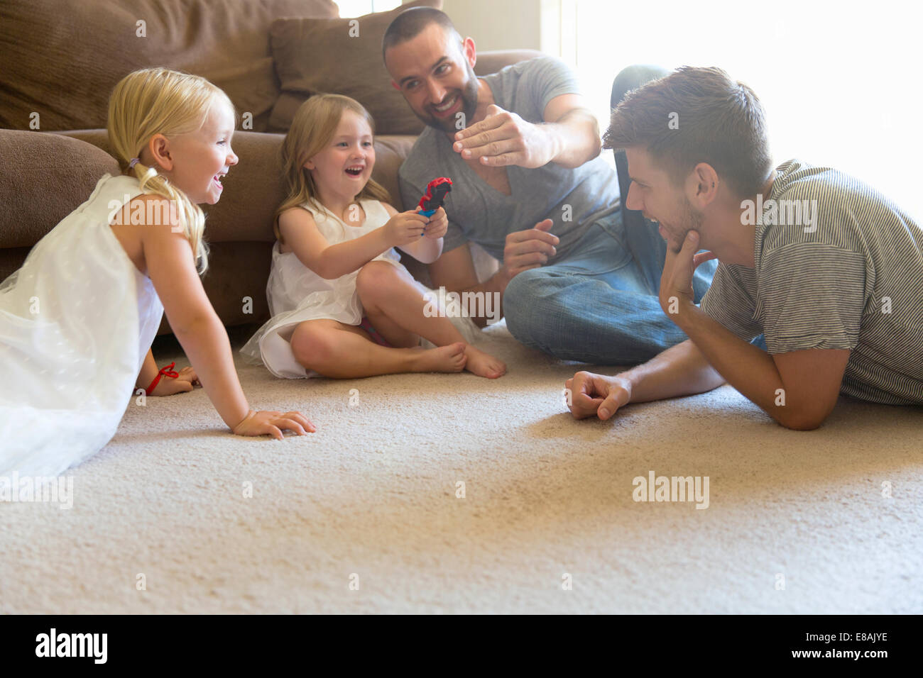 Male couple and two daughters playing on sitting room floor - Stock Image