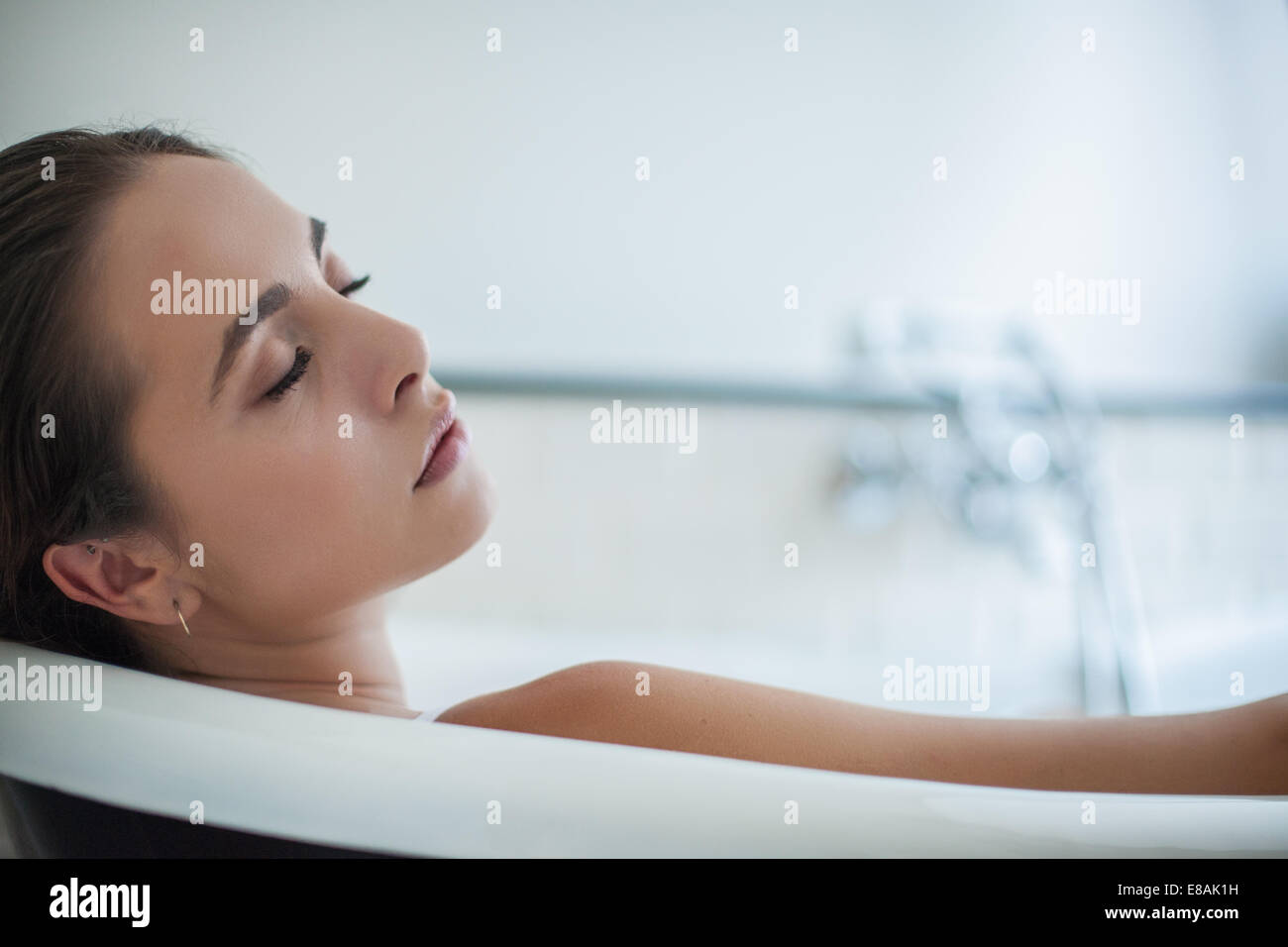 Close up of serene young woman asleep in bath - Stock Image